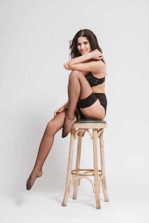 Full length portrait of an attracive brunette woman in lingerie and stockings sitting on chair and posing isolated on a white background