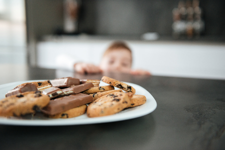 Image of little boy standing in kitchen while tries to eating cookies and chocolate. Focus on cookies. Stock Photo