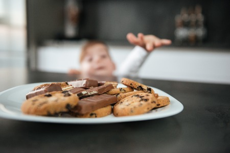 Picture of little cute boy standing in kitchen while tries to eating cookies and chocolate. Focus on cookies. Stock Photo