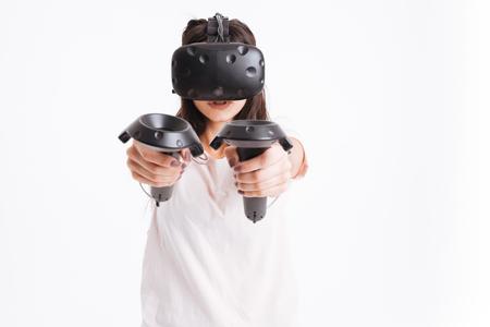 白い背景の上のジョイスティックを保持する仮想現実デバイスを身に着けている非常に若い女性のイメージ。 写真素材