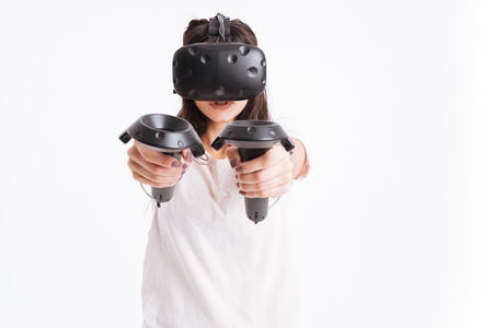 Image of pretty young lady wearing virtual reality device holding joysticks over white background.
