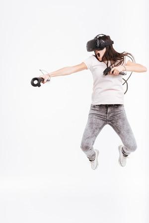Photo de jolie jeune femme portant le dispositif de réalité virtuelle tenant des joysticks et de sauter sur fond blanc. Banque d'images - 75585166