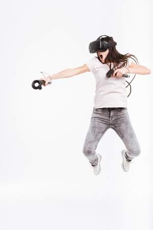 Photo of pretty young woman wearing virtual reality device holding joysticks and jumping over white background.