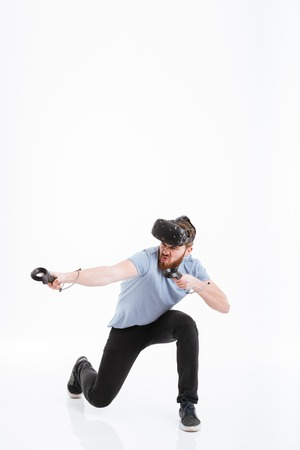 Image of bearded playful man wearing virtual reality device over white background.