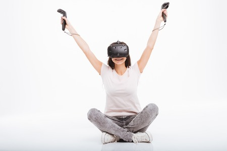 Image of joyful young woman wearing virtual reality device holding joysticks sitting over white background. Stock Photo
