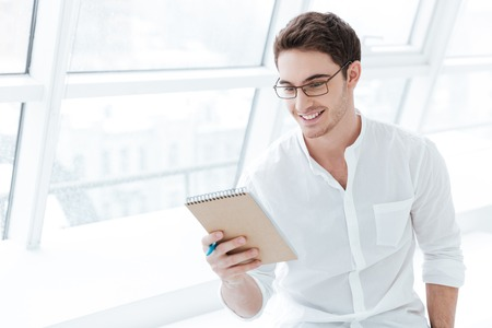 Photo of handsome man wearing eyeglasses and dressed in white shirt holding tablet computer over big white window background. Looking at tablet. Stock Photo