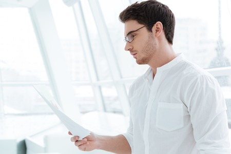 Photo of handsome man dressed in white shirt holding documents near big white window.