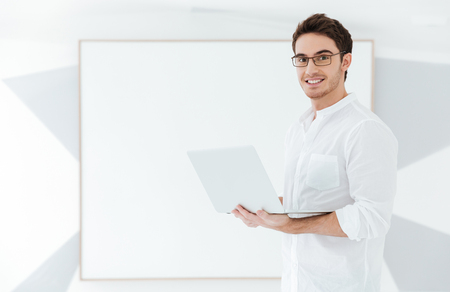 Image of cheerful man wearing eyeglasses and dressed in white shirt using laptop computer near big board. Look at camera. Stock Photo