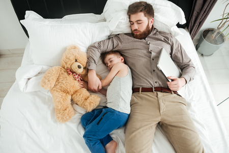 Image of cute little boy sleeping at home in bed with his bearded father and toy.