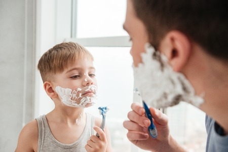 Image of funny father and son are applying shaving foam on their faces and smiling while shaving in bathroom Stock Photo