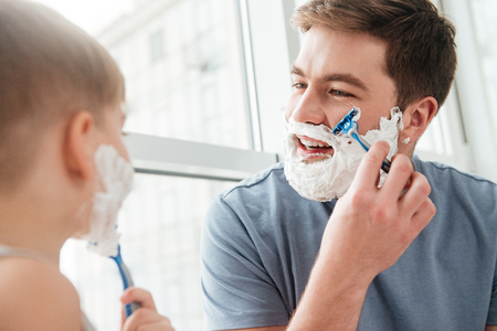 Photo of happy handsome father and son are applying shaving foam on their faces and smiling while shaving in bathroom