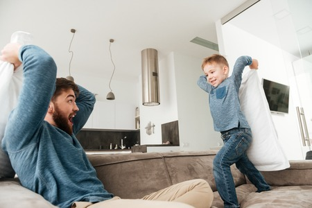 Image of attractive young father fighting by pillows with his little cute son. Imagens