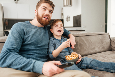 Image of cheerful father holding remote control while watching TV with his little cute son holding popcorn.