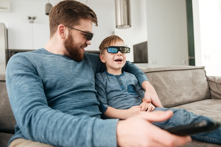 Cheerful bearded young father holding remote control while watching TV with his little cute son using 3d glasses. Imagens