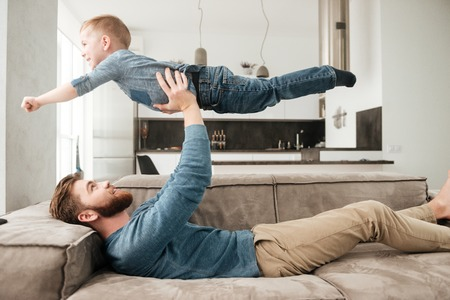 Image of happy bearded father playing on sofa with his little cute son.