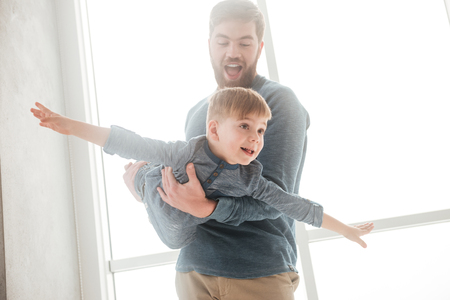 Photo of little boy playing at home with his bearded father.