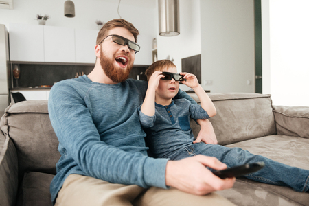 Image of happy bearded father holding remote control while watching TV with his little cute son using 3d glasses. Imagens