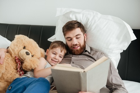 Image of boy lies at home in bed near toy with his bearded father reading fairytale book. Imagens