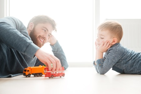 Picture of little boy playing on the floor with his bearded father.