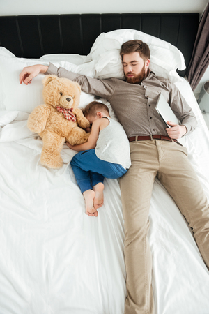 Photo of cute little boy sleeping at home in bed with his bearded father and toy.