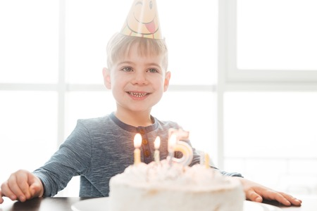 Photo of little cute happy birthday boy sitting in kitchen near cake while smiling. Look aside. Stock Photo