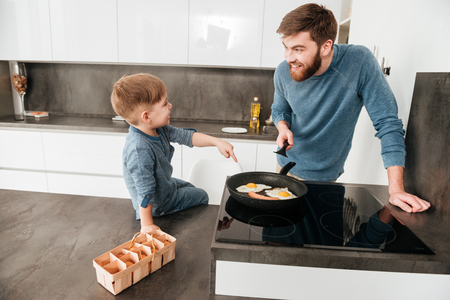 tot: Photo of handsome bearded father dressed in blue sweater cooking at kitchen with his little cute son Stock Photo