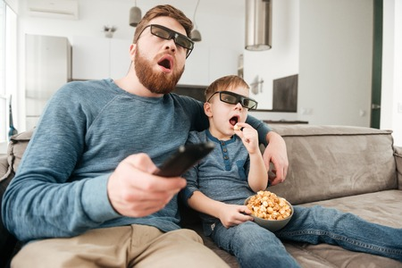Confused happy father holding remote control while watching TV with his little cute son using 3d glasses holding popcorn.