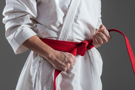 Cropped photo of young sportsman dressed in kimono practice in karate while tightening red belt isolated over grey background. Stock Photo