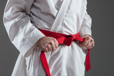 Cropped image of sportsman dressed in kimono practice in karate while tightening red belt isolated over grey background. Stock Photo