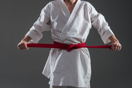 sensei: Cropped image of sportsman dressed in kimono practice in karate while tightening red belt isolated over grey background. Stock Photo