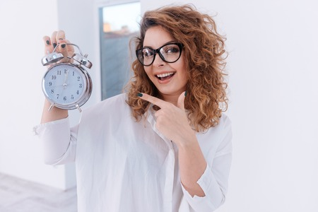 Woman in glasses and white shirt holding clock and pointing on them over white background