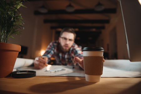 tired businessman: Tired bearded man trying to reach coffee cup while working on desk with graphs, focus on coffee cup