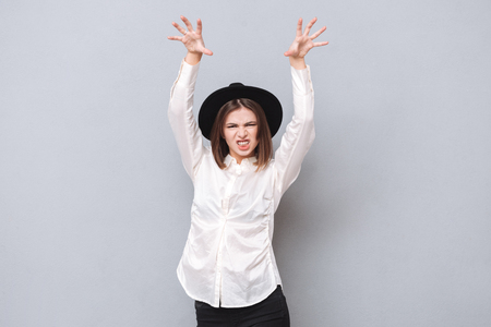 Portrait of a scary angry woman making cat claws gesture with hands raised isolated on the gray background