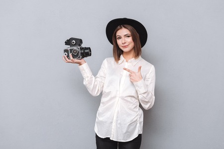 Portrait of a smiling hipster girl in hat standing and pointing finger at retro video camera isolated on the gray background Stock Photo