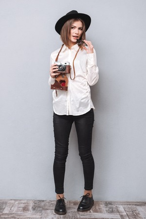 full shot: Full length portrait of a young hipster girl in hat standing and holding retro camera isolated on the gray background Stock Photo