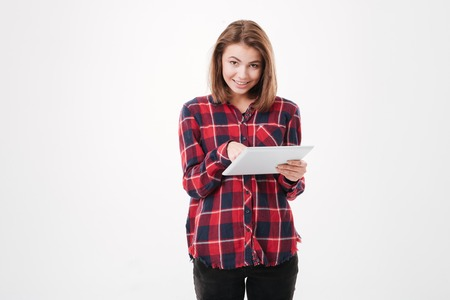joy pad: Portrait of a pretty smiling girl in plaid shirt using tablet computer isolated on a white background