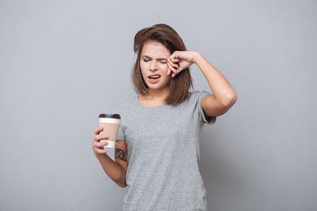 Portrait of a tired sleepy girl in t-shirt yawning isolated on a gray background