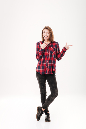 Full length portrait of surprised attractive young woman with opened mouth pointing finger away over white background