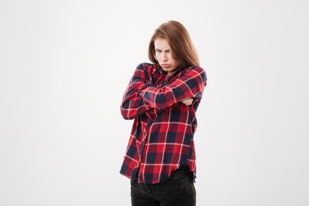 Pretty sad offended girl in plaid shirt standing with hands crossed over white background