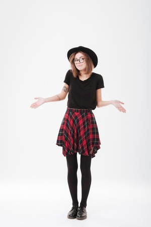 indecisive: Full length portrait of a young stylish girl in hat standing and shrugging shoulders isolated on a white background