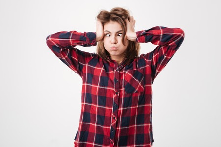 Young funny woman in plaid shirt making crazy face isolated on white background Фото со стока