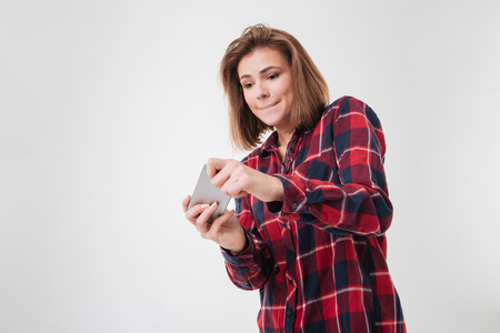 Portrait of a young casual teenage girl in plaid shirt playing on mobile phone over white background Stock Photo