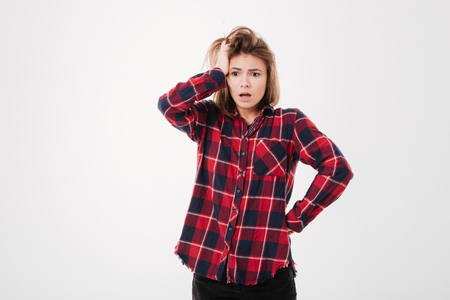 Portrait of a confused pretty girl in plaid shirt isolated on a white background Stock Photo
