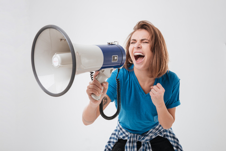 Portrait of a young casual woman screaming in megaphone isolated on a white background