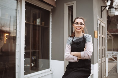 patty cake: Image of happy young lady confectioner with long hair standing with arms crossed near cafe outdoors. Look at camera. Stock Photo
