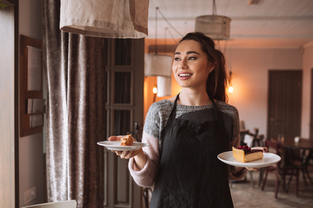 patty cake: Image of beautiful young woman confectioner with long hair standing in cafe while holding cake in hands.