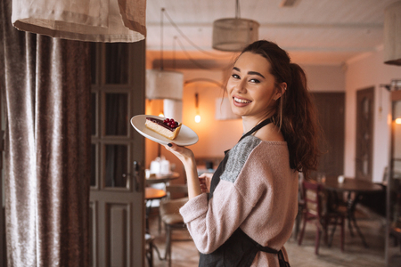 patty cake: Back view photo of young lady confectioner with long hair standing in cafe while holding cake in hands. Look at camera. Stock Photo