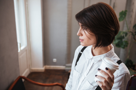Authoress in white shirt holding cup of coffee in hand and looking away Stock Photo