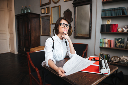 Authoress in glasses and white shirt sitting by the table with paper and typewriter and looking up Фото со стока