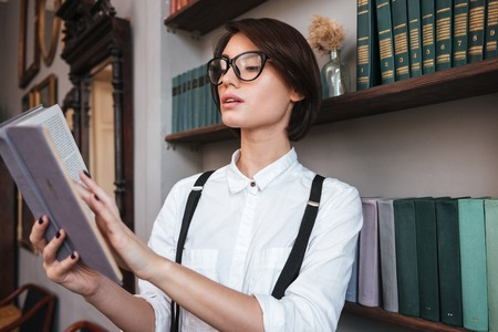 concentrate on: Authoress in glasses and shirt reading book near the bookshelf Stock Photo